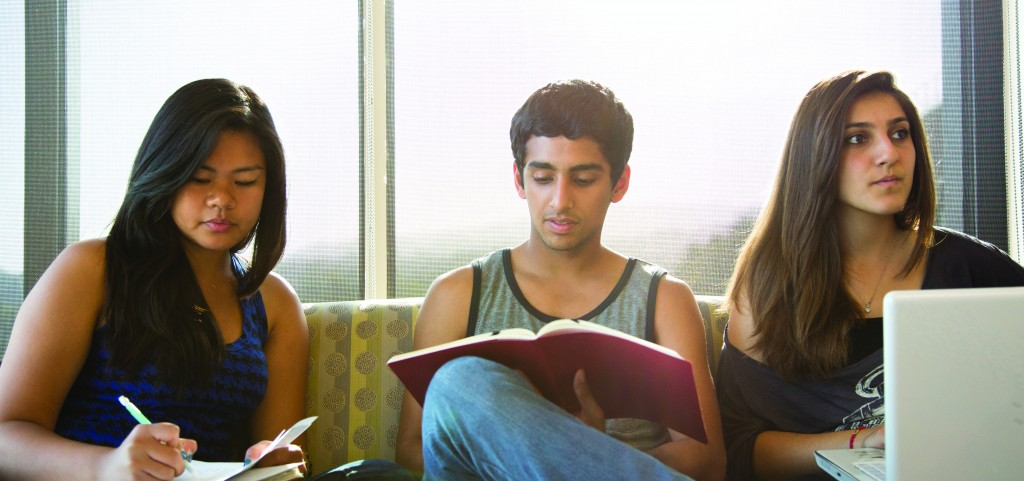 Three students study in the lounge of Gardenia Way, one of the De Neve Plaza residence halls.